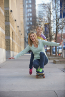 Caucasian mother and daughter riding skateboard on sidewalk