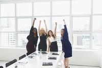 Businesswomen cheering in conference room
