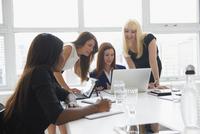 Businesswomen using laptop in office meeting