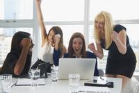 Businesswomen cheering at laptop in office meeting