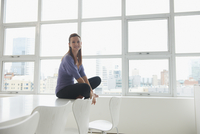 Caucasian businesswoman sitting on conference table in office
