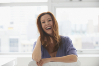 Caucasian businesswoman laughing at window