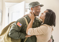Close up of woman kissing returning soldier