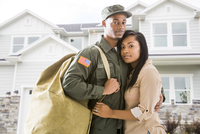 Returning soldier and wife standing outside house