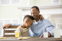 Black father and son hugging at table in backyard
