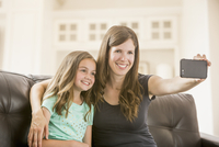 Caucasian mother and daughter taking selfie with cell phone on sofa