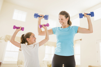 Caucasian mother and daughter lifting weights