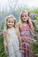 Caucasian sisters standing in tall grass