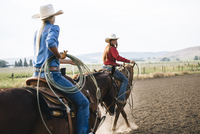 Caucasian cowgirls riding horses on ranch