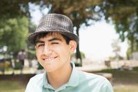 Hispanic teenage boy smiling in park