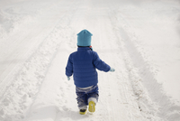 Caucasian boy walking in tire tracks in snow