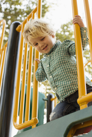 Caucasian boy on play structure in playground