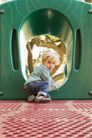 Caucasian boy climbing on play structure in playground