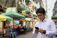Asian businessman using cell phone in city