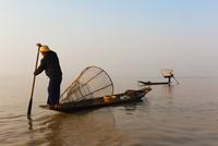 Asian fisherman rowing canoe on still lake