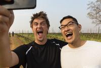 Men taking selfie with cell phone in vineyard