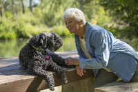 Older Caucasian woman sitting with dog in park