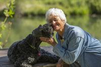 Older Caucasian woman hugging dog in park