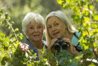 Older Caucasian women bird-watching outdoors