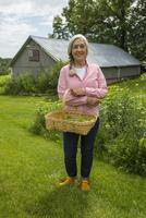 Caucasian woman carrying basket of vegetables in garden