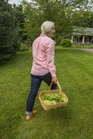 Caucasian woman carrying basket of vegetables in backyard