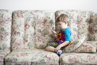 Boy playing with cell phone on sofa