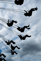 Silhouette of people riding chair swing under cloudy sky