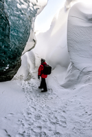 Hiker walking in snowy ice cave