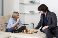 Caucasian father and son playing chess on sofa