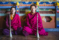 Asian monks sitting on temple floor