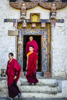 Asian monks walking out temple doorway