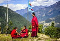 Asian monks with flag on remote hilltop