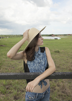 Caucasian woman leaning on fence in rural pasture