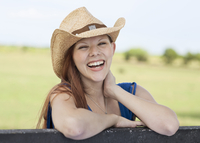 Caucasian woman laughing on fence in rural pasture