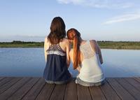 Caucasian women sitting on wooden dock over lake