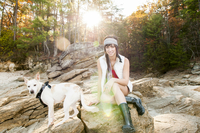 Caucasian woman and dog sitting in forest