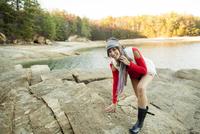 Caucasian woman climbing rocks near lake