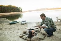 Man building campfire at lake