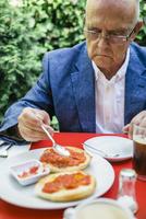 Hispanic businessman eating breakfast outdoors