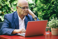 Hispanic businessman using laptop outdoors