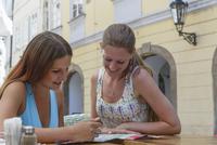 Caucasian women reading at sidewalk cafe