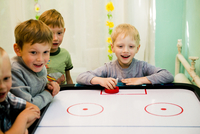 Caucasian boys playing air hockey