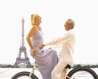 Caucasian couple riding bicycle near Eiffel Tower, Paris, Ile