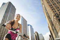 Hispanic woman riding bicycle under highrise buildings