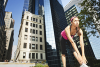 Hispanic woman stretching under highrise buildings