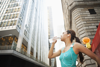 Hispanic woman drinking water bottle under highrise buildings