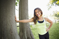 Mixed race woman leaning on tree