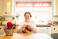 Caucasian woman knitting in kitchen