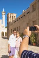 Caucasian tourist photographing couple