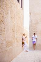 Caucasian couple standing under stone walls
